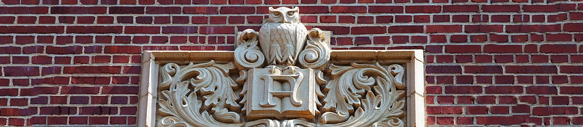 A stonework owl and book emblem on the outside Eppes Hall