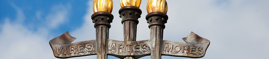 Photo of the top of the University Center's three torches fountain of Vires, Artes, Mores