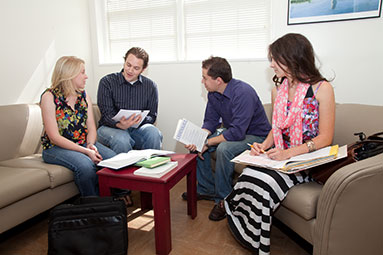 Photo of students meeting and conversing in a study room on campus